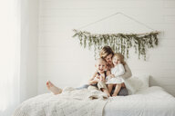Happy mother with children sitting on bed at home - CAVF51446