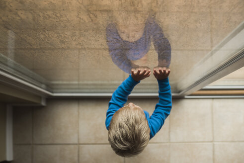 High angle view of baby boy looking through window while standing at home - CAVF51452