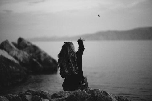 Girl sitting on rocks, throwing stones in the water - INGF03451