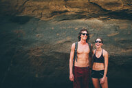 Couple posing against rock face, Canoa, Manabi, Ecuador - CUF46324