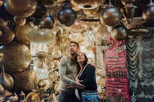 Pregnant couple in souk, Marrakech, Morocco - CUF46327
