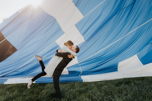 Newly engaged couple kissing, hot air balloon in background - CUF46330
