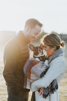 Couple carrying their puppy in woollen blanket - CUF46333
