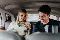 Bride and bridegroom in backseat of car - CUF46339