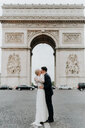 Bride and bridegroom kissing, Arc de Triomphe in background, Paris, France - CUF46342