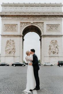 Bride and bridegroom kissing, Arc de Triomphe in background, Paris, France - CUF46342