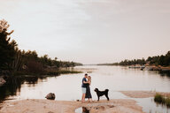 Couple enjoying view of river with pet dog, Algonquin Park, Canada - CUF46357