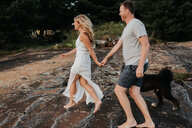 Couple walking with pet dog, Algonquin Park, Canada - CUF46360