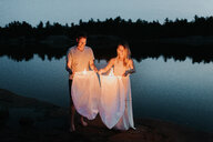 Couple releasing sky lanterns by lake, Algonquin Park, Canada - CUF46366