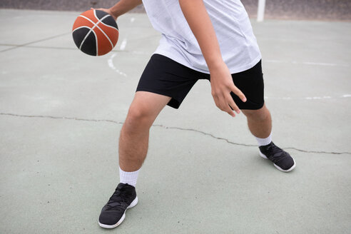 Male teenage basketball player playing basketball on court, waist down - CUF46450