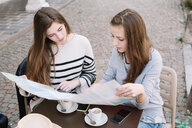 Girlfriends reading street map at cafe - CUF46462
