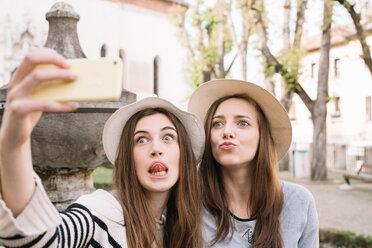 Girlfriends taking selfie at piazza, Belluno, Veneto, Italy - CUF46465