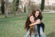 Girlfriends playing piggyback ride in park - CUF46468