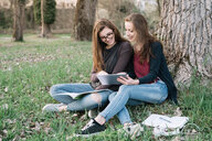 Girlfriends reading book in park - CUF46471