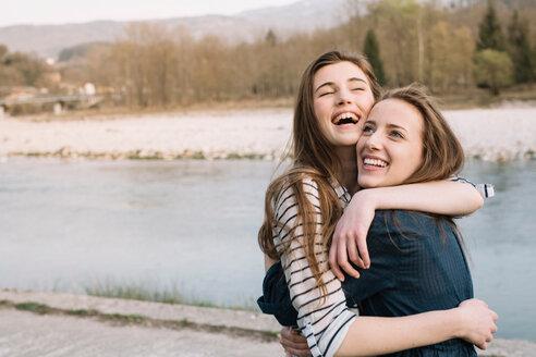 Happy girlfriends by river, Belluno, Veneto, Italy - CUF46474