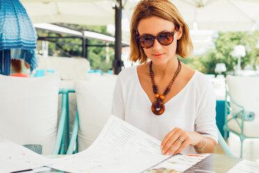 Woman reading menu on terrace - CUF46483