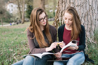 Girlfriends reading book in park - CUF46495
