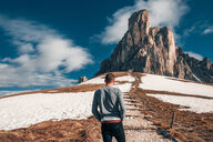 Man standing steps to rock, Francenigo, Veneto, Italy - CUF46498