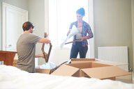 Couple packing mirror into cardboard box - CUF46519