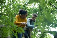 Hiker couple looking over wooden bridge - CUF46534