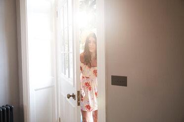 Stylish woman opening hotel door into lobby - CUF46552