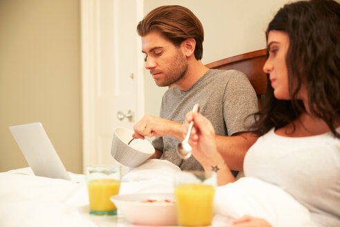 Couple using laptop while having fruit and orange juice breakfast in bed - CUF46558
