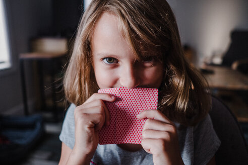 Girl hiding behind playing cards in living room, portrait - ISF20041