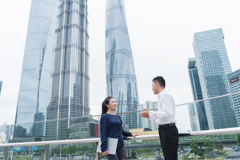Young businesswoman and man talking in city financial district, Shanghai, China - ISF20074