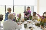 Active seniors enjoying flower arranging class - CAIF22171