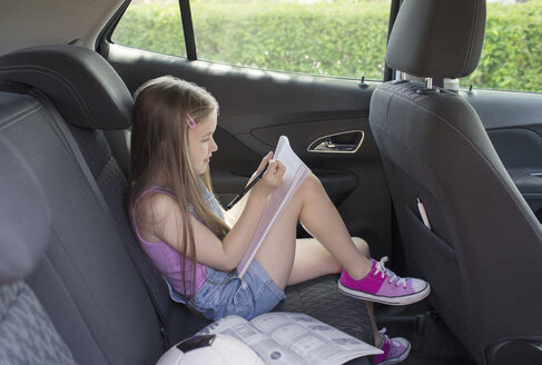 Girl doing homework in back seat of car - CAIF22189