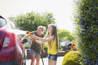 Mother and daughter washing car in sunny driveway - CAIF22195