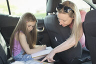 Mother helping daughter doing homework in back seat of car - CAIF22198
