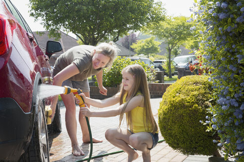 Mother and daughter washing car in sunny driveway - CAIF22201
