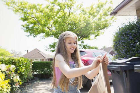 Girl recycling in sunny driveway - CAIF22204