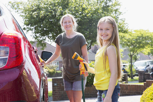 Portrait smiling mother and daughter washing car in sunny driveway - CAIF22207