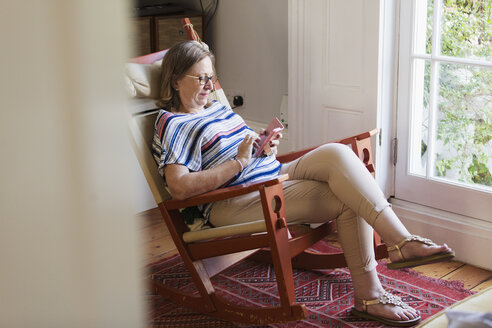 Senior woman texting with smart phone in rocking chair - CAIF22219