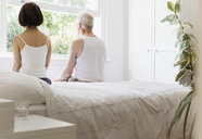Thoughtful senior couple sitting on bed looking out window - CAIF22225