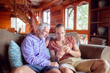 Father and son using smart phone on cabin sofa - CAIF22240