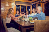 Friends toasting red wine glasses, enjoying dinner at cabin dining room table - CAIF22249