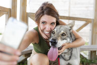 Young woman taking selfie with her dog with smartphone - WPEF01074