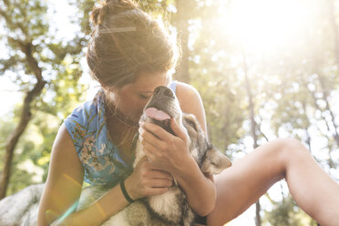 Young woman cuddling her dog in the woods - WPEF01080
