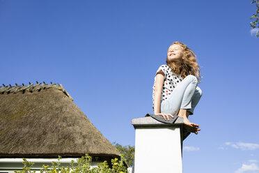 Girl sitting on a wall under blue sky - OJF00265
