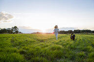 Girl with a dog running over a field at sunset - OJF00271