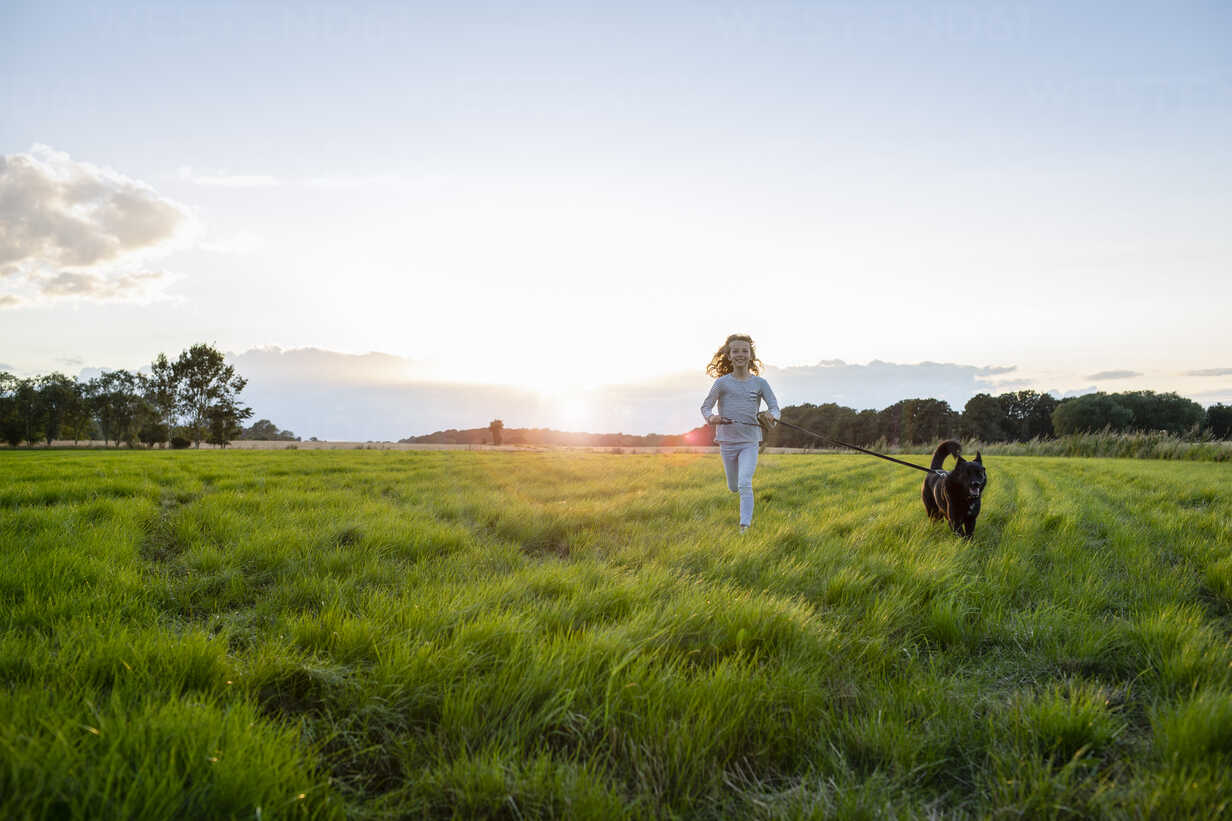Girl with a dog running over a field at sunset - OJF00271 - Julia Otto/Westend61