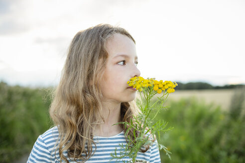 Girl in nature smelling at a wild flower - OJF00274