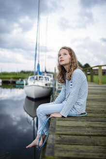 Girl sitting on a jetty in a small harbor - OJF00277