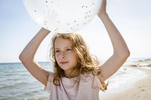 Girl holding a balloon at the beach - OJF00286