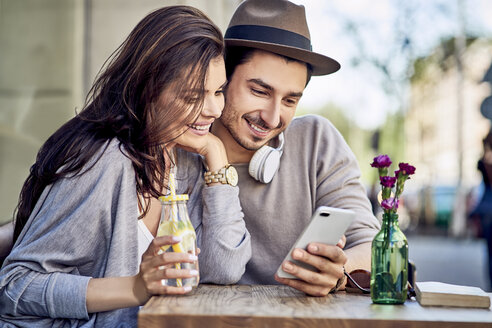 Happy young couple looking at cell phone at outdoors cafe - BSZF00786