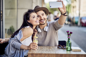 Happy young couple taking a selfie at outdoors cafe - BSZF00789