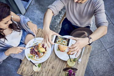 Overhead view of couple taking photo of food at outdoors restaurant - BSZF00801